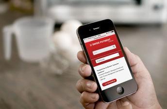 Eine Hand hält ein iPhone 4s, welches die mobile Version der Website des Swiss Payment Forums zeigt.
